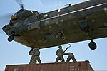 U.S. Soldiers with the 390th Seaport Operations Company (SPOC) connect the reach pendants from a sling-loaded shipping container onto a CH-47 Chinook helicopter during the joint-service SPOC 13-2 training 130804-A-GT254-013.jpg