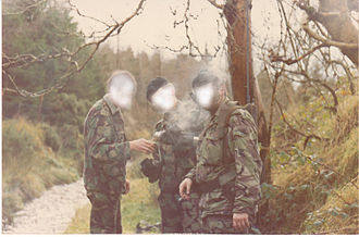 Ulster Defence Regiment - Soldiers of 11 UDR on a patrol break in the South Armagh area. The soldier on the right is carrying a jamming device to prevent the detonation of radio-controlled improvised explosive devices.