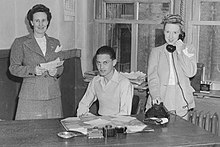 A young man seated flanked by two women standing, all of them behind a desk. The woman on the right is holding a telephone; the one on the left is holding what appears to be correspondence.