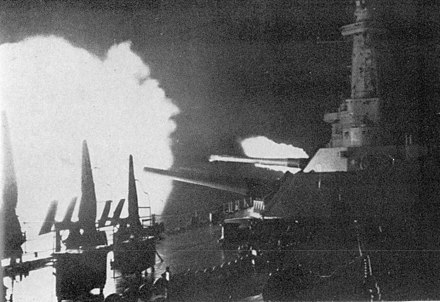 Two large gun turrets are trained to starboard, with the superstructure in the background. Flames are shooting out of one or more of the guns in both the nearer of the two turrets and an unseen gun astern.