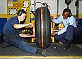 US Navy 030618-N-3970R-003 Aviation Structural Mechanic 3rd Class Nichalos Baldwin and Aviation Structural Mechanic 2nd Class Eddie Brutus work together to properly torque the fittings on an aircraft tire.jpg