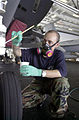 US Navy 030716-N-0413R-008 Aviation Structural Mechanic 3rd Class Ivan Irizarry of Harlem, N.Y., applies a coat of paint to the nose landing gear of an aircraft, in the Hanger Bay aboard USS Nimitz (CVN 68).jpg