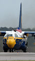 US Navy 050416-N-0295M-137 A crew member aboard the U.S. Marine Corps C-130 Hercules Fat Albert, assigned to the U.S. Navy Blue Angels flight demonstration team, proudly waves an American flag while taxing.jpg