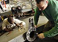 US Navy 060905-N-9742R-093 Aviation Structural Mechanic 3rd Class Kenrick Gentle, left, and Aviation Structural Mechanic 2nd Class Ryan Vanzanten change a bonding wire in a horizontal stabilizer for an F-A-18C Hornet.jpg