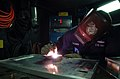 US Navy 070123-N-4940H-001 Hull Maintenance Technician 3rd Class Peter Solomon welds a television bracket together in the Machine Shop aboard the Nimitz-class aircraft carrier USS John C. Stennis (CVN 74).jpg