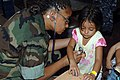 US Navy 090626-F-1333S-022 Lt. Cmdr. Yolanda Mitchell-Lee, embarked aboard the Military Sealift Command hospital ship USNS Comfort (T-AH 20), examines a child during a Continuing Promise 2009 medical community service project.jpg