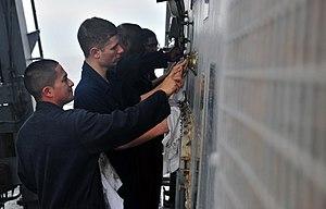 US Navy 120124-N-OP638-029 Sailors scrub the bulkhead during an all-hands preservation call.jpg
