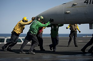 US Navy 120215-N-DR144-429 Sailors perform an aircraft pushback to position an F-A-18C Hornet on the flight deck of the Nimitz-class aircraft carri.jpg