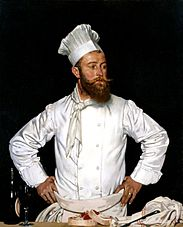 A chef with a bushy brown beard and waxed moustache wearing his white kitchen attire and a tall chef's hat stands with his hands on his hips as if he has been interrupted in his work.