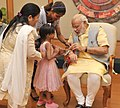 Women and Children from various segments of society tying 'Rakhi' on the Prime Minister, Shri Narendra Modi's wrist, on the occasion of 'Raksha Bandhan', in New Delhi on August 29, 2015.jpg