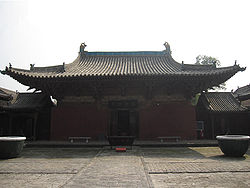 The Wanfo Hall of Zhenguo Temple. The tiled roof is decorated with small, ornate dragons. There is one door opening to a bricked courtyard