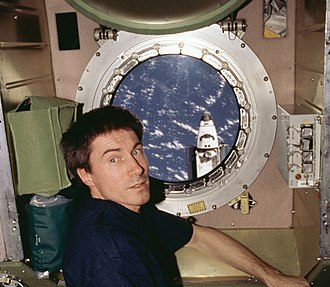 Expedition 1 - S. K. Krikalev in the Zvezda module. Atlantis is shown outside the window, flying mission STS-98. (NASA)