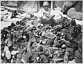 """Pfc. Robert Askew...with the 3278th Quartermaster Company, examines overshoes which have been turned in. Overshoes prov - NARA - 531412.jpg"