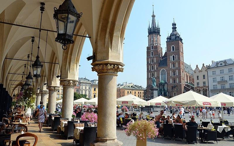 Vue sur l'église Sainte Marie (Kosciol Mariacki) de Cracovie depuis les arcades de la Halle aux draps (Sukiennice). Photo de Silar.