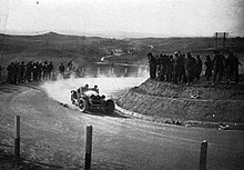 An old sports car drives on unsealed roads as people stand on hills around the road and watch