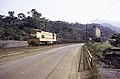 ASC Leiden - F. van der Kraaij Collection - 13 - 008 - LAMCO J.V. Conveyor belt to silos. Locomotive nr. 303 with wagons loaded with iron ore - Yekepa, Nimba county, Liberia - 1976.jpg