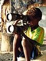 A small boy holds up huge binoculars on Savo Island, Solomon Islands. (10663258524).jpg