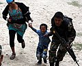 A woman and her child being escorted by the Nepalese Army personnel during a rescue mission in the quake hit Nepal.jpg