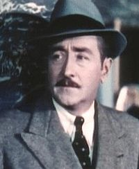 Adolphe Menjou i Skandal i Hollywood (1937).