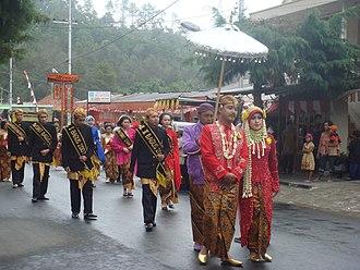 "Magetan Regency - The Labuh Sesaji, or ""throwing of offering"" procession proceeds towards Lake Sarangan where offerings will be thrown"