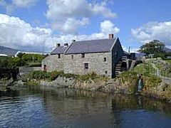 Old, slate-roofed, grey stone mill building, situated beside a small river.