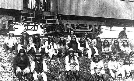Band of Apache Indian prisoners at rest stop beside Southern Pacific Railway, near Nueces River, Texas. (Geronimo is third from the right, in front), September 10, 1886. Apache prisoners.jpg