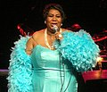 A woman stands on stage and sings into a microphone. She wears a blue dress and has a blue feather boa around her arms.