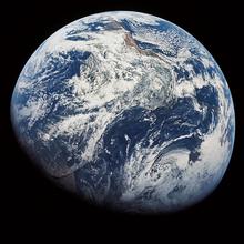 Fotografia da Terra quase totalmente iluminada pelo Sol, exibindo principalmente a cobertura de nuvens sobre o Oceano Atlântico e a América do Sul. A coloração azul dos oceanos domina a imagem.