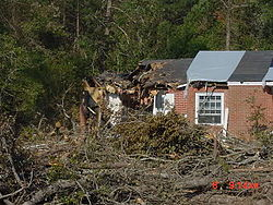 A brick home with part of its roof collapsed due to fallen trees.