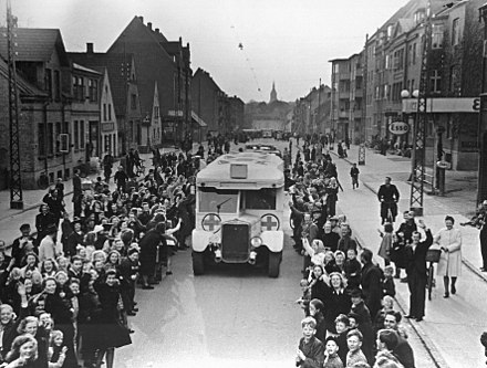 A White Bus passes through Odense, Denmark, 17 April 1945 Bernadotte-aktionen. Danske Rode Kors busser korer gennem Odense d. 17. april 1945 pa vej til Sverige med danske fanger fra tyske koncentrationslejre (7392607518).jpg