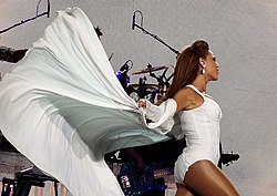 A brunette woman is singing while she holds a microphone with both hands. She wears a white short dress that has a long cape and sheer stockings.