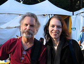 A bearded man who looks to be in his 60s wearing a dark red shirt and Welch, smiling, with her arm around him. Huge white tents are in the background.