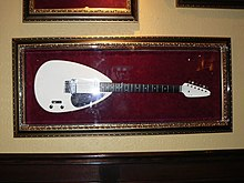 A white teardrop shaped guitar as used by Brian Jones, on display at the Hard Rock Cafe in Sacramento, California