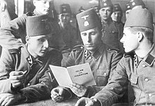 three soldiers in SS uniform and wearing fez headgear reading a pamphlet