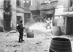 A black and white photograph of a German Verbrennungskommando soldiers using a flamethrower to set fire to ruins of a Warsaw building.