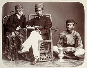 Pesantren - Studio Portrait of a Pesantren teacher (center) with his student (left) and an employee. Dutch colonial period.