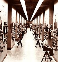 Control panels and operators for calutrons at the Y-12 Plant in Oak Ridge, Tennessee.