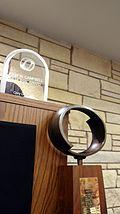 Ligna trofeo kun metalovalo sur pinto staranta antaŭ podio, kiu havas pleksiglas-trofeon sur pinto