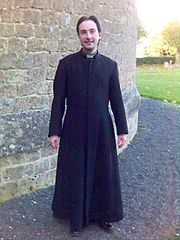 An Anglican priest wearing a single-breasted cassock.