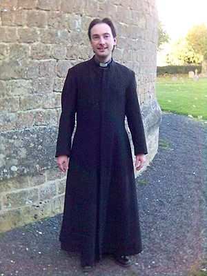 An Anglican priest wearing a single-breasted c...