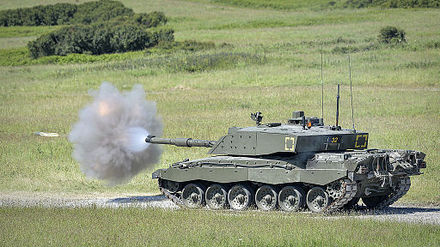 A Challenger 2 firing its main armament during an exercise. The shell is visible to the left of the smoke cloud.