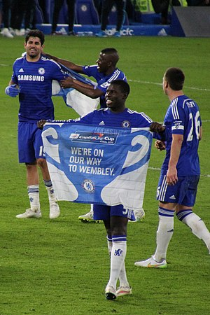 Kurt Zouma - Zouma holding a banner celebrating Chelsea reaching the 2015 Football League Cup Final