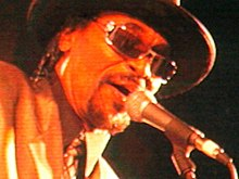 A close-up of Brown singing into a microphone