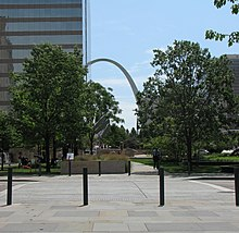 Four black bollards sit in the foreground, trees are visible in the middle, and in the distant background, a tall grey arch peeks out from behind office buildings.