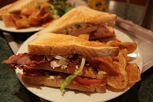 A club sandwich (Chicken, bacon, salad, etc), ...