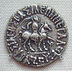 """Azes I - Coin of Azes I. Obv: Azes I in military dress, on a horse, with couched spear. Greek legend: BASILEOS BASILEON MEGALOU AZOU """"of the Great King of Kings Azes"""". British Museum."""