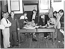 A soldier is sitting at a wooden table, with two men signing papers at the table and a line of men lined up on the right. On the left are two men, one in shirt and tie and the other in a suit facing the camera.