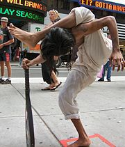 Ravi the Scorpion Mystic stands on one leg performing his act in Times Square, NYC, 2004