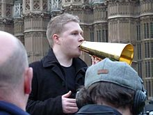 A picture of Dan Bull in Parliament Square, holding a handheld megaphone, standing on a raised platform and addressing protesters
