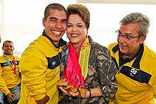 Two men wearing yellow outfits standing next to a woman with medals around her neck.